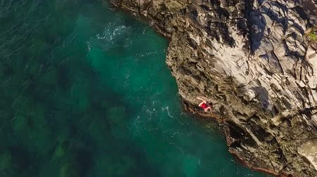 cliff : Cliff Jumping into Ocean. Aerial View Slow Motion. Young Man Jumps off Cliff Into Blue Ocean. Summer Extreme Sports Outdoor Lifestyle. Stock Footage