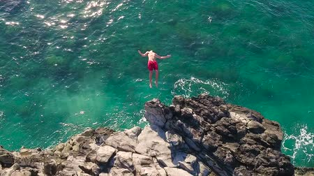 altura : Aerial View of Cliff Jumping into Ocean. Young Man Jumps off Cliff Into Blue Ocean. Summer Extreme Sports Outdoor Lifestyle.