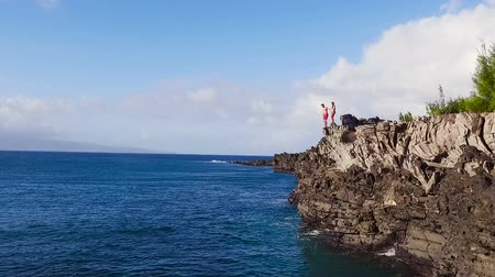cliff : Aerial View of Cliff Jumping into Ocean. Young Couple Jumps off Cliff Into Blue Ocean. Summer Extreme Sports Outdoor Lifestyle.