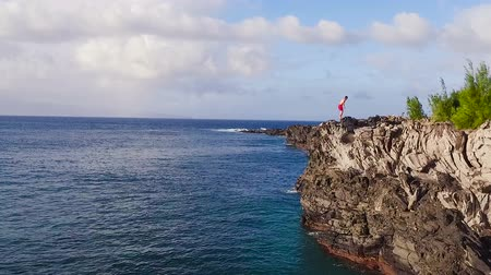 cliff : Aerial View of Cliff Jumping into Ocean. Young Man Jumps off Cliff Into Blue Ocean. Summer Extreme Sports Outdoor Lifestyle.