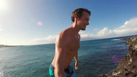 экстремальный : POV Slow Motion Cliff Jumping Backflip. Athletic Young Man Jumping From Cliff Into Ocean. Adventure Extreme Sports Lifestyle Hobby Vacation