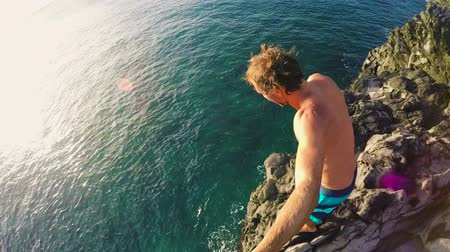 tiro : POV Slow Motion Sunset Cliff Jumping. Athletic Young Man Jumping From Cliff Into Ocean. Adventure Extreme Sports Lifestyle Hobby Vacation