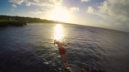 cliff : Slow Motion Cliff Jumping Backflip at Sunset. Athletic Young Man Jumping From Cliff Into Ocean. Adventure Extreme Sports Lifestyle Hobby Vacation