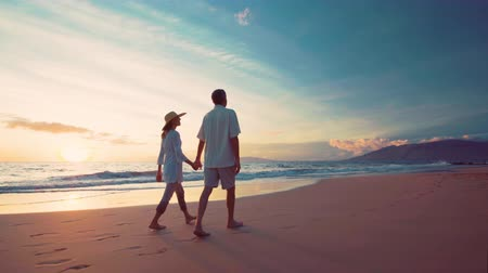 régi : Retirement Vacation on Luxury Tropical Beach at Sunset. Older Couple Holds Hands Getting Their Feet Wet