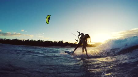 deski : Extreme Kitesurfing down Big Ocean Wave at Sunset. Summer Ocean Sport in Slow Motion. Girl Kite Surfing in Bikini Wideo
