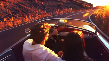 sport : Happy Couple Driving on Country Road into the Sunset in Classic Vintage Sports Car