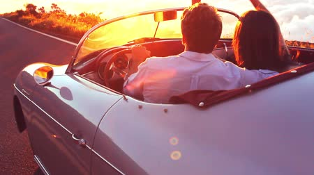 samochody : Happy Couple Driving on Country Road into the Sunset in Classic Vintage Sports Car