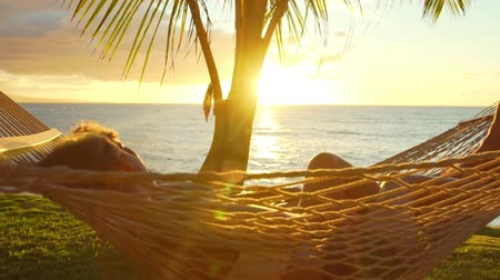 гамак : Romantic couple relaxing in tropical hammock at sunset. Summer Luxury Vacation. Стоковые видеозаписи