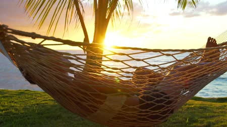 vacation destination : Romantic couple relaxing in tropical hammock at sunset. Summer Luxury Vacation. Stock Footage