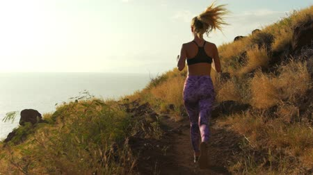 sportowiec : Young Athletic Woman Running on Mountain Trail. POV Follow Cam. Sunset Workout in Nature.