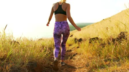 sportowiec : Young Athletic Woman Walking on Mountain Trail. Sunset Workout in Nature.