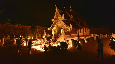 храмы : 4k, timelapse, Ton Kwen Temple, Chiangmai, Thailand 10 May, 2017: People light candles and pray at the Ton Kwen Temple on Visakha Bucha day. Noise and high ISO clip