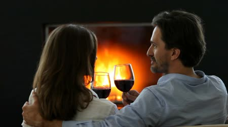 na zdraví : Happy couple clinking red wine glasses near fireplace
