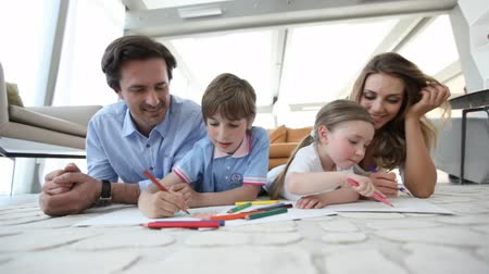 parenthood : Happy parents drawing with their children