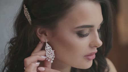 biżuteria : Beautiful bride puts on earring getting ready for wedding