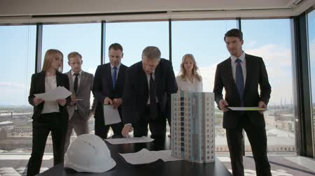 housing problems : Business meeting of architects and investors looking at model of modern multi storey residential building house on table Stock Footage