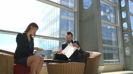 Two smiling business people discussing documents sitting in a lobby of a modern building