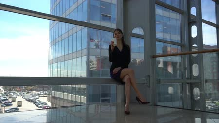Business woman having break with takeaway coffee sitting in a modern place