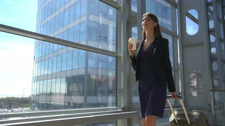 Beautiful young business woman with coffee walking with a suitcase in airport terminal Stok Video