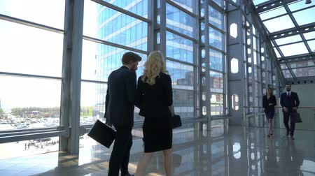 Business people walking in modern glass office building