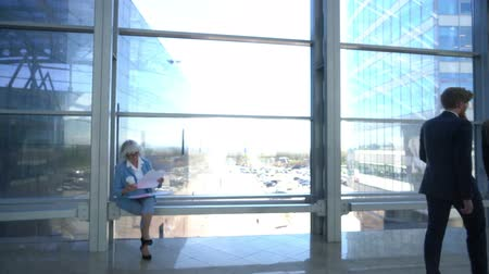 Business people walking in modern glass office building, senior business woman reading documents Stok Video