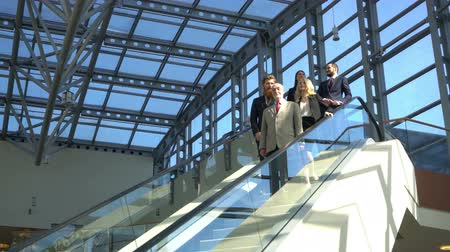 Group of business people on escalator in modern glass office building Stok Video