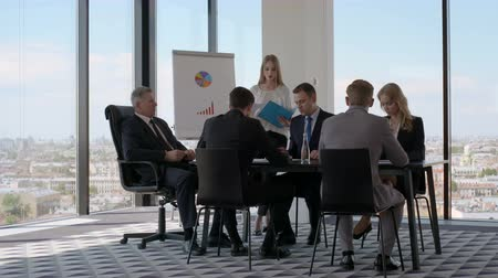 Business people sitting around meeting table, talking and working with documents