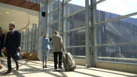 Two senior people walking together with a suitcase in airport terminal