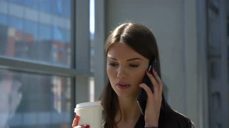 Attractive young businesswoman calling on mobile phone, walking inside office building holding a cup of coffee