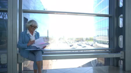 Senior business woman reading documents at coffee break in office building hall, other business people walking around