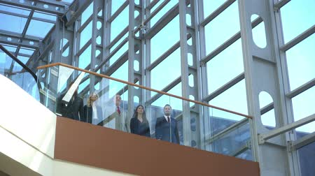 Business team showing thumbs up standing on a balcony