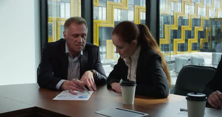 Mature business man and his young female collegue sitting at meeting table in office and discussing financial diagrams Stok Video