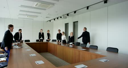 Mature businesswoman in formal meeting room and shaking hands with collegue