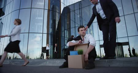 Fired business man sitting on the street near office building with box of his belongings. He lost work. Other businessman comforts and encourages him