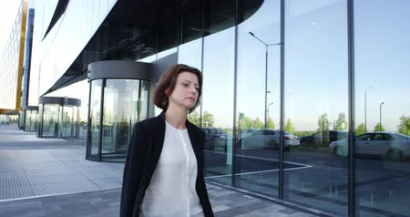 Mature businesswoman walking outdoors along modern office building Stok Video