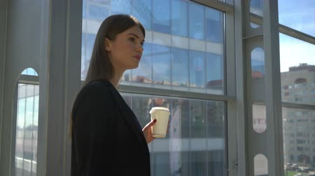 Beautiful young business woman drinking coffee and thinking at a break in modern office Stok Video