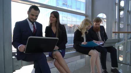 Smiling coworkers discussing work project while on coffee break in office building