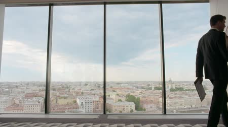 Business people walking in office building with panoramic windows with view at city