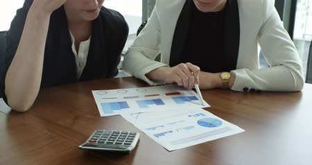 diagrama : Business people pointing at diagrams discussing financial reports at workplace