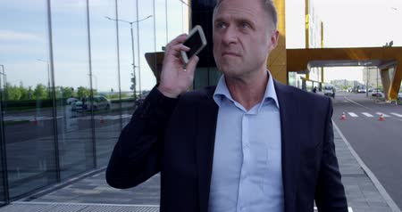 Mature business man walking outdoors along office building and talking on phone Stok Video