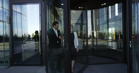 Two business people leaving building through a spinning door and talking
