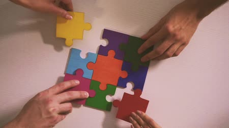 головоломки : Business people join puzzle pieces in office. Concept of teamwork and partnership