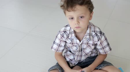 menino : Portrait sad little boy sitting on the floor at home