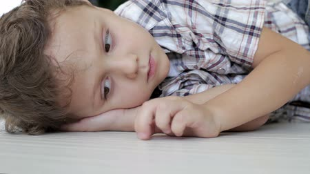 unott : Portrait sad little boy lying on the floor at home Stock mozgókép