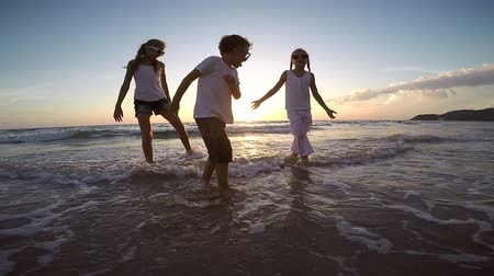 ailelerin : Happy children playing on the beach at the sunset time. Concept of happy friendly family.
