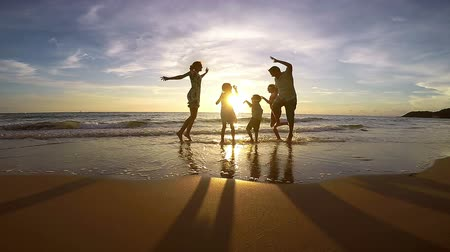 Silhouette of happy family who playing on the beach at the sunset time. Concept of friendly family. Stok Video