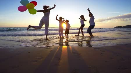 sunset sea : Silhouette of happy family who playing on the beach at the sunset time. Concept of friendly family. Stock Footage