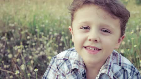 hareketli : Portrait happy little boy sitting in the park Stok Video