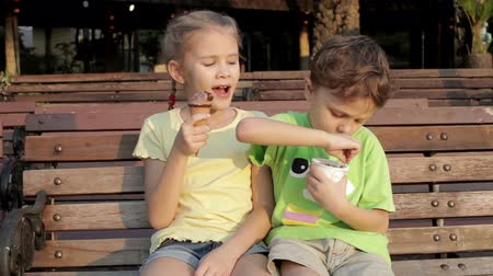 küçük kız : Two happy children eating ice cream on bench in the park at the day time. Concept healthy food.