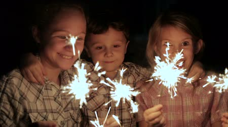 Новый год : Happy kids standing on the road and burning sparkles at the night time. Concept Brother and Sister Together Forever Стоковые видеозаписи